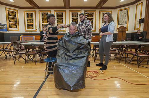 Bridgehampton School seniors Jada Pinckney, Daniel Denton and Hayley Lund were called up to finish history teacher John Reilly's new 'do as part of a fundraising event for a family in the district. Photo by Michael Heller.