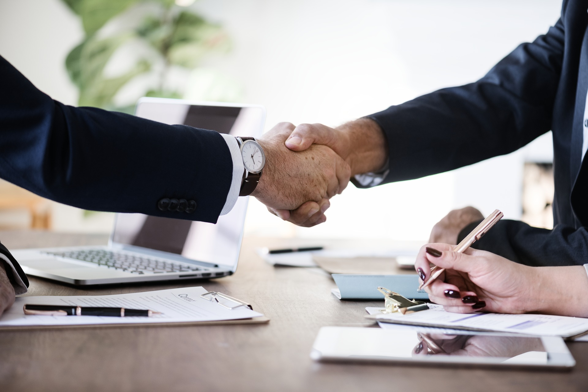 business people hands shaking over table