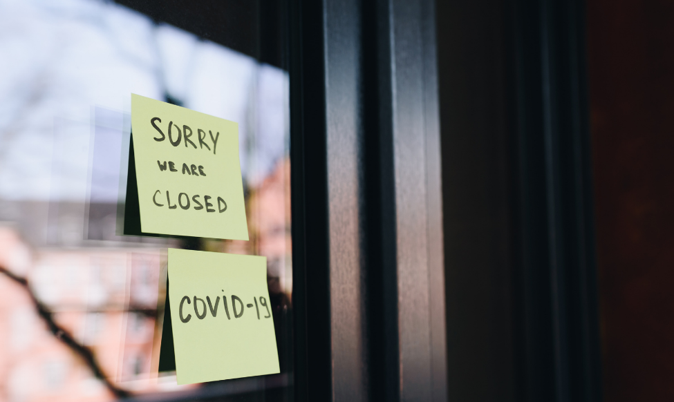 """business door with """"closed: COVID-19"""" sign"""